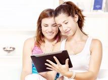 Due adolescenti felici che per mezzo del calcolatore del touchpad Immagini Stock
