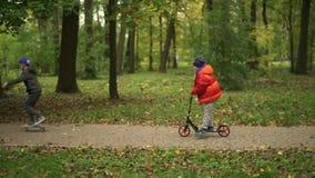 Due adolescenti guidano un motorino e un bordo del penny Si muovono lungo il percorso nel parco Giorno di autunno nel parco, verd video d archivio