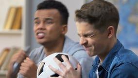 Due adolescenti si sono rovesciati con la partita di perdita di campionato di sport del gruppo favorito stock footage