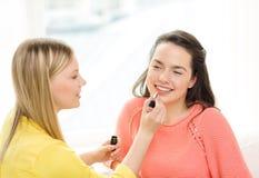 Due adolescenti sorridenti che stendono il trucco a casa Fotografia Stock