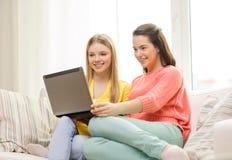 Due adolescenti sorridenti con il computer portatile a casa Immagini Stock Libere da Diritti