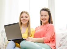 Due adolescenti sorridenti con il computer portatile a casa Fotografia Stock Libera da Diritti