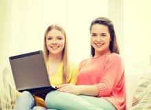 Due adolescenti sorridenti con il computer portatile a casa Fotografie Stock Libere da Diritti
