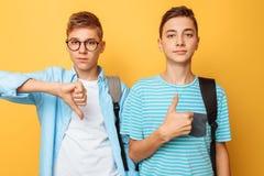 Due adolescenti, tipi mostrano le emozioni opposte, amici mostrano i gesti positivi e negativi, su un fondo giallo fotografia stock