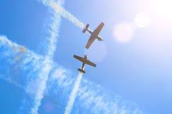 Due aerei leggeri del motore con una traccia di fumo bianco volano nel cielo blu Fotografia Stock