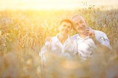 Due agricoltori anziani che si siedono nel giacimento di grano Fotografia Stock