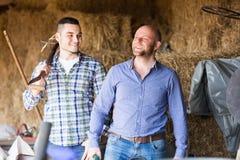 Due agricoltori che lavorano nel granaio Fotografie Stock