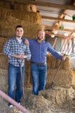 Due agricoltori che lavorano nel granaio Immagine Stock