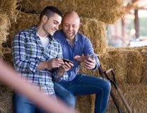 Due agricoltori con i telefoni al hayloft Fotografie Stock