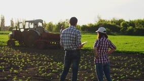 Due agricoltori parlano nel campo, utilizzano una compressa video d archivio