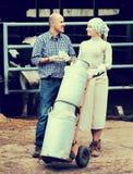 Due agricoltori sorridenti che tengono un carrello con latte Fotografia Stock
