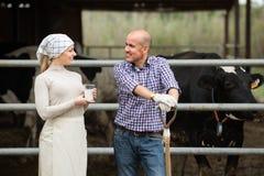 Due agricoltori in stalla con bicchiere di latte Fotografia Stock