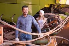 Due agricoltori vicino al trattore enorme Immagine Stock