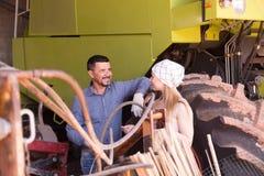Due agricoltori vicino al trattore enorme Fotografia Stock
