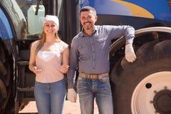 Due agricoltori vicino al trattore enorme Fotografia Stock Libera da Diritti