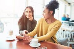 Due allegri e le belle ragazze stanno sedendo insieme vicino alla tavola e stanno guardando qualcosa sul telefono Guardano Immagini Stock