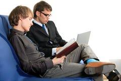 Due allievi con il taccuino ed il computer portatile. Immagini Stock