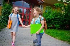 Due allievi della scuola elementare, ragazzo e ragazza, su un cortile della scuola Fotografia Stock