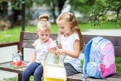 Due allievi hanno letto i libri su un banco Il concetto della scuola, studio, istruzione, amicizia, infanzia fotografie stock libere da diritti