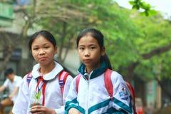 Due allievi stanno camminando alla scuola sulla via della città di Nam Dinh nel Nord del Vietnam Immagine Stock