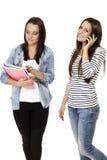 Due allievi uno che appendono sul telefono Immagini Stock Libere da Diritti
