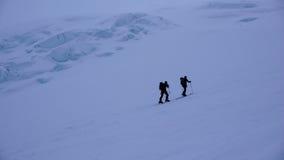 Due alpinisti maschii dello sci su una mattina nebbiosa scura nelle alpi svizzere intestate allo Strahlhorn Fotografie Stock