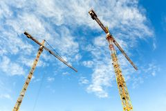 Due alte gru a torre lavorano alla costruzione di nuove case Immagine Stock Libera da Diritti