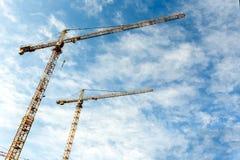 Due alte gru a torre lavorano a costruzione di nuove case Immagini Stock