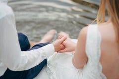 Due amanti che si siedono sul ponte Fotografie Stock