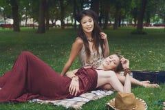 Due amiche alla moda eleganti di boho felice con la chitarra, picnic Immagine Stock