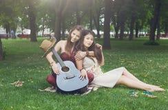 Due amiche alla moda eleganti di boho felice fanno un picnic in parco Fotografie Stock Libere da Diritti