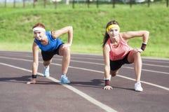 Due amiche caucasiche che hanno allungamento degli esercizi sulla sede di sport all'aperto Immagini Stock Libere da Diritti