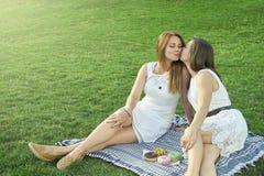 Due amiche che baciano sulla via fotografie stock