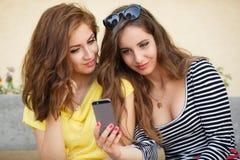 Due amiche che guardano le foto sul telefono cellulare Fotografie Stock Libere da Diritti