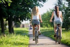 Due amiche che guidano le biciclette Fotografia Stock