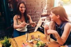 Due amiche che hanno pranzo sano in caffè Giovane donna che prende immagine di alimento con l'invio dello smartphone sui media so immagini stock libere da diritti