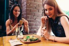 Due amiche che hanno pranzo sano in caffè Giovane donna che prende immagine di alimento con l'invio dello smartphone sui media so fotografia stock