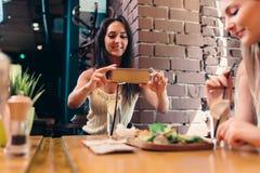 Due amiche che hanno pranzo sano in caffè Giovane donna che prende immagine di alimento con l'invio dello smartphone sui media so fotografia stock libera da diritti