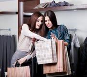 Due amici comprano i vestiti ai tassi tagliati nel deposito fotografia stock