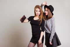 Due amiche felici allegre fotografate sul telefono, telefono della ragazza di auto Fotografia Stock