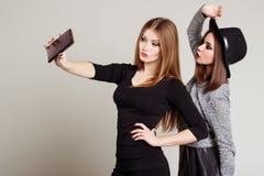 Due amiche felici allegre fotografate sul telefono, telefono della ragazza di auto Fotografie Stock