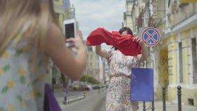 Due amiche felici divertendosi sulla via insieme La ragazza che prende foto del suo amico sul cellulare dopo la compera stock footage