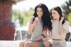 Due amiche guardano il video sullo smartphone Immagini Stock Libere da Diritti