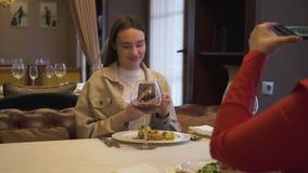 Due amiche positive che si siedono nel ristorante moderno, insieme Le donne moderne prendono le foto del loro alimento in stock footage