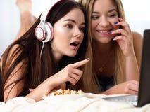 Due amiche sorridenti felici mangiano il popcorn fotografia stock