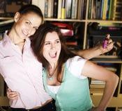 Due amiche sveglie che prendono foto se stessi in biblioteca, concetto della gente di stile di vita Fotografie Stock