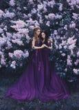 Due amiche, un biondo e un castana, con amore che si abbraccia Fondo di bello giardino lilla di fioritura Il Princ fotografie stock