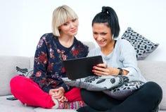 Due amici attraenti della donna con la compressa Fotografia Stock Libera da Diritti