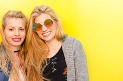 Due amici biondi degli studenti che ridono facendo uso del telefono cellulare in una parete gialla Fotografia Stock Libera da Diritti