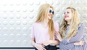 due amici biondi delle studentesse che ridono facendo uso del telefono cellulare e della compressa Fotografia Stock